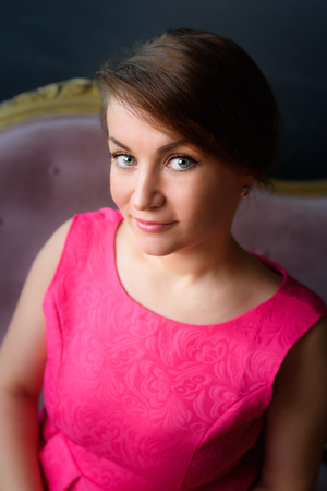 Beautiful girl in pink looks at the camera Stock Photo