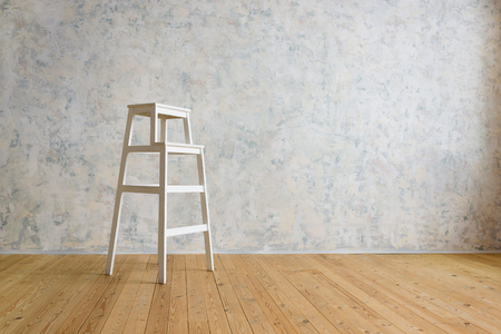 A wooden stepladder stands in a room with a white wall