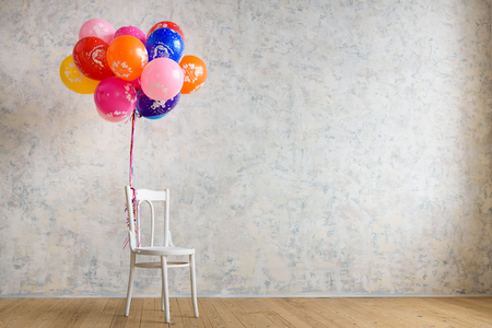 Chair and balloons on the wooden floor in the room