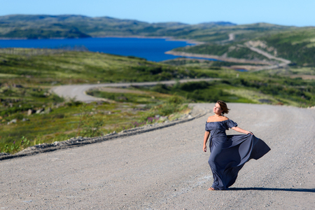 The girl in the dress is standing on the road
