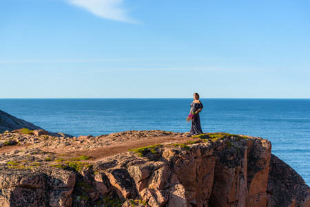 Girl in a dress on the edge of a cliff