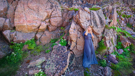 Girl in a long dress against the background of a rock