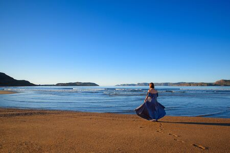A girl in a dress is standing by the sea