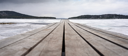 wooden bridge and lake, covered with ice Stock Photo