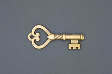 old ornate golden decorative key, vintage design element, isolated object, close-up, top view, flat lay on the black grungy background