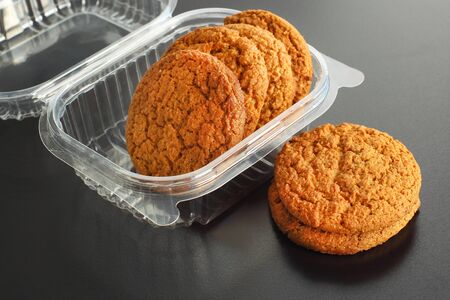 オートミール クッキーは黒い背景の上に透明なコンテナー