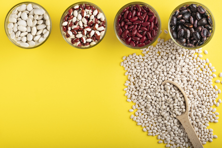 Colored bean in glass jars and wooden spoon of white bean on a yellow background. Image with copy space.
