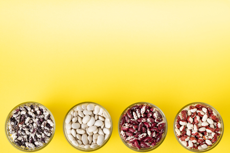 Colored bean in glass jars on a yellow background. Image with copy space. Stock Photo