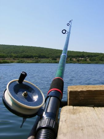 Rod for fishing with the reel on the background of the lake and green forests Stock Photo