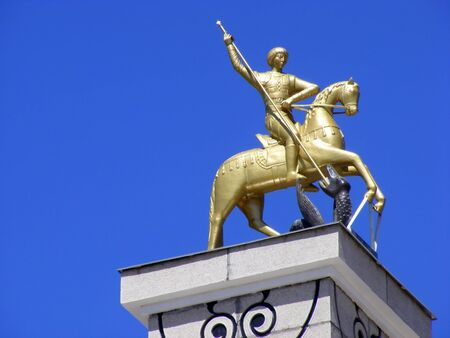 The  monument to St. George mounted on a rectangular column on the background of blue sky