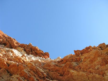 Sheer cliff of layered rocks on the mountain backdrop of blue sky  Stock Photo