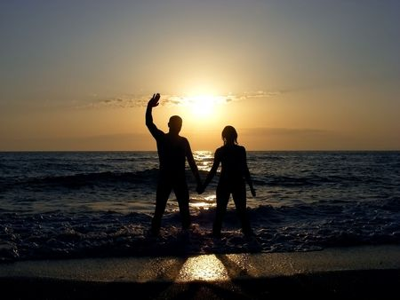 Man and woman at sunset in the waves of ocean surf at the beach