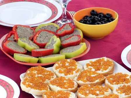 White dish with sandwiches with red caviar is on the red tablecloth