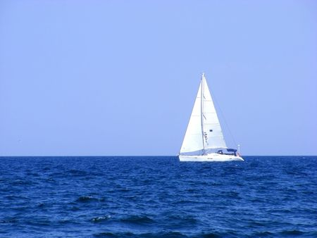 Sailing yacht with triangular sails of white sails on the waves of the sea on the horizon Stock Photo