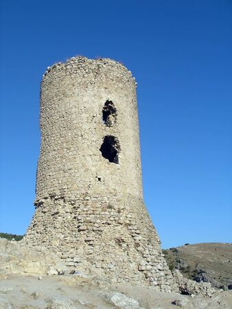 Ancient tower with windows partially destroyed in the background of blue sky Stock Photo