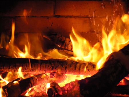 Wood fire in the fireplace, sparks fly on both sides Stock Photo