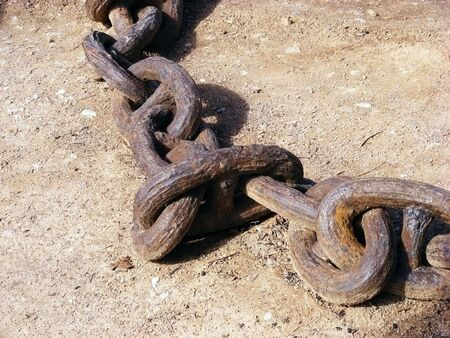 Old anchor chain with large links of rusty iron lies on the shore Stock Photo