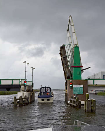 drawbridge: Boat passing under an open drawbridge Editorial