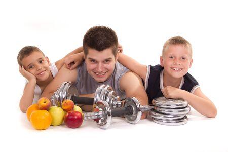 lift hands: dos ni�os y un hombre de descanso despu�s de un entrenamiento con frutas Foto de archivo