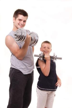 fils et le jeune homme sain exercent à la gym