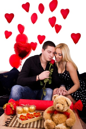 Young couple in love with a room full of heart shaped balloons. photo
