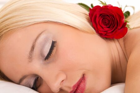Attractive woman asleep with rose placed on her shoulder. photo