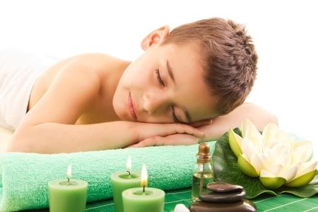 garçon se repose avec spa sur la table de massage
