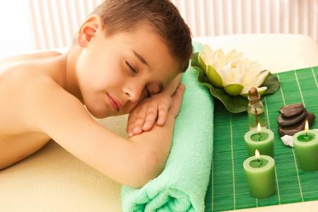 niño se apoya con spa en la mesa de masaje Foto de archivo