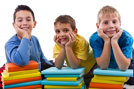 smiling young boys with piles of books Stock Photo