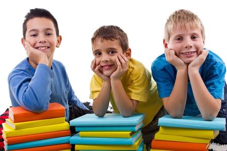 sourire de jeunes garçons avec des piles de livres Banque d'images
