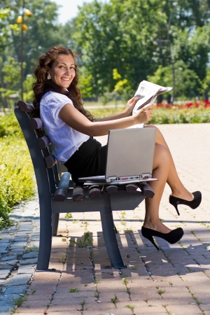Successful business woman sitting on a park bench and reading newspaper photo