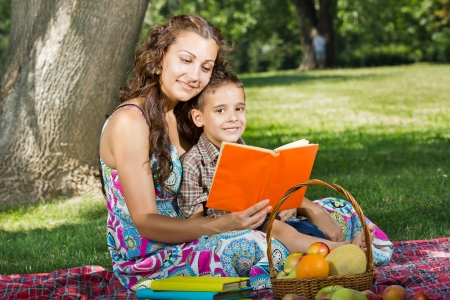 beautiful mother and little boy reading book together photo