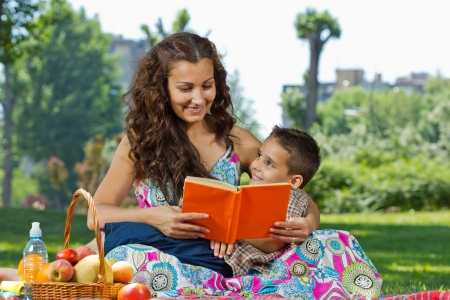 Mother and little boy reading book together photo