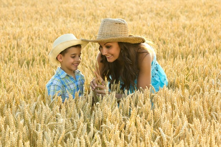 mom plays with her son in a wheat field photo
