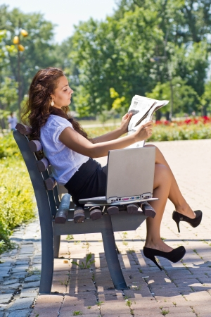 Successful business woman sitting on a park bench, working on a laptop and reading newspaper photo