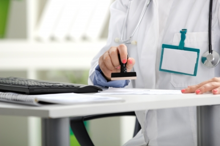 female doctor putting stamp on a document Stock Photo - 20705767