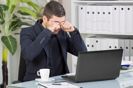 exerted: business man looking at laptop, receiving bad news