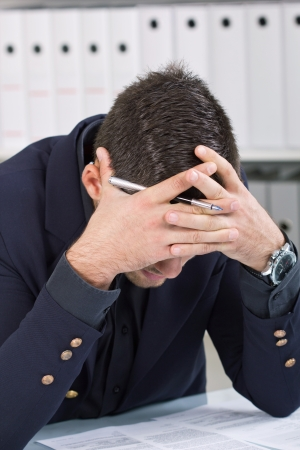 exerted: young business man a headache from too much work Stock Photo