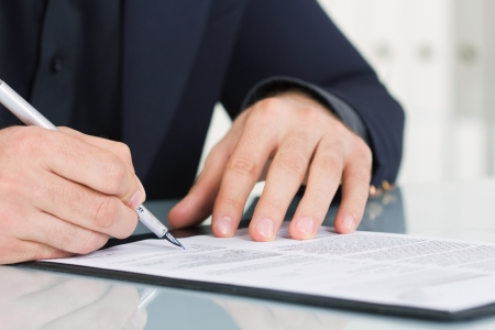 businessman  sitting at office desk signing a contract photo