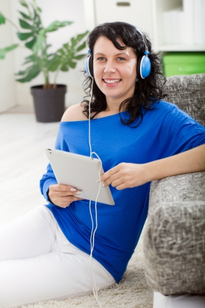 modern girl with electronic tablet and headphones at home enjoy in music Stock Photo - 20685195