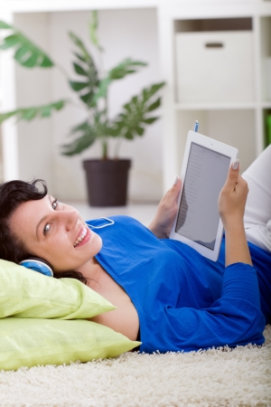 young smiling  woman with tablet  and headphones at home photo