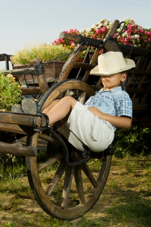 Jeune garçon de dormir dans le jardin sur le vieux chariot