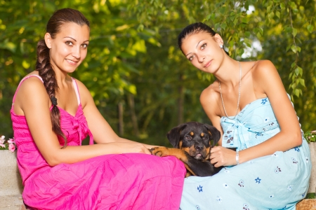 two  beautiful sisters with  rottweiler  puppy in park photo