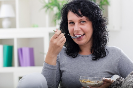 tenager:  beautiful woman siting on sofa at home,eating cereals