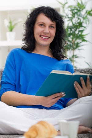 young woman resting at home, reading a book Stock Photo - 21502274
