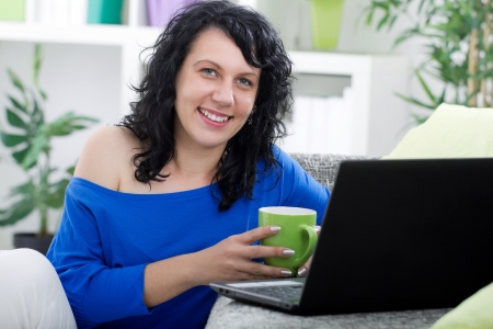 tenager: woman sitting at her home drinking coffe, smiling