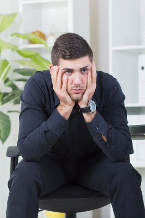 exerted: Senior businessman sitting in a chair worried about job Stock Photo