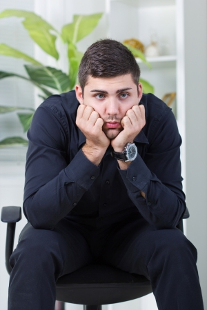 exerted: young businessman sitting in a chair worried about job Stock Photo