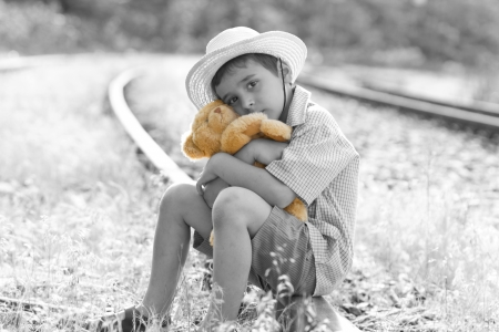 lonely orphan child sitting on the railroad Stock Photo - 21879107