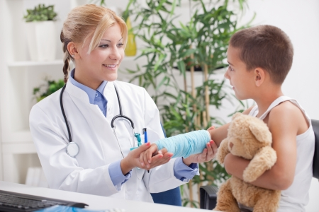 litle: doctor examines an injured hand a little boy in office